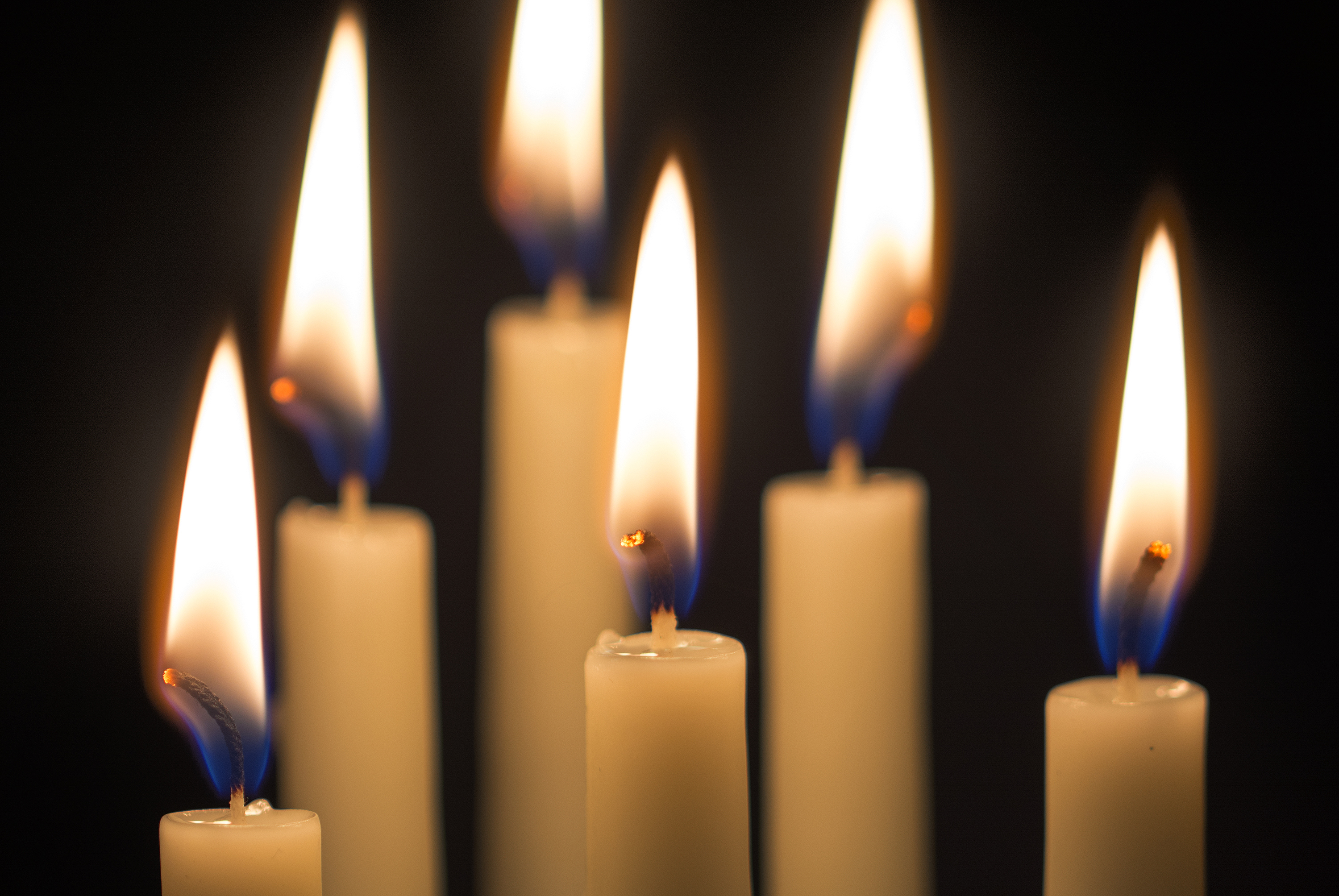 group of six burning candles against black background, selected